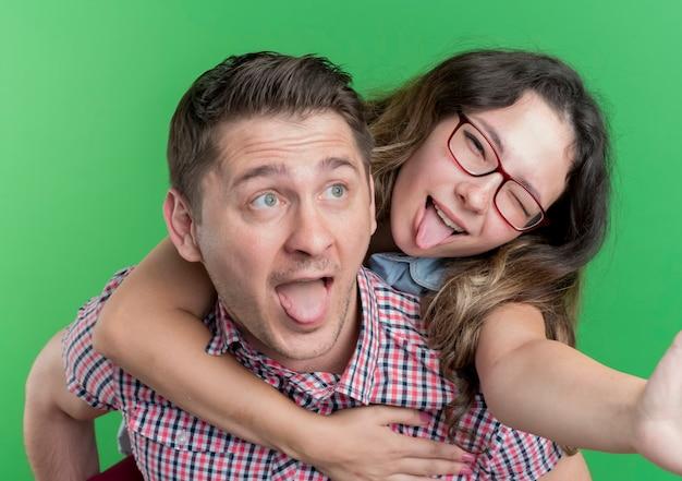 Молодая пара мужчина и женщина в повседневной одежде, счастливые в любви, обнимаются, веселятся вместе, стоя над зеленой стеной