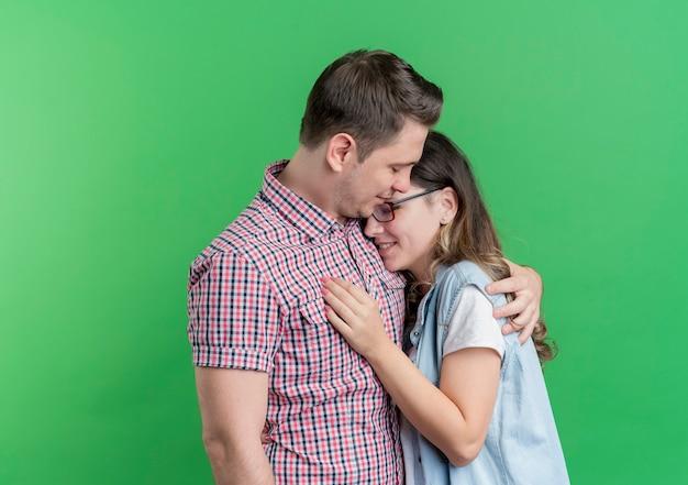 녹색 벽 위에 서 포옹 사랑에 행복 캐주얼 옷에 젊은 부부 남녀