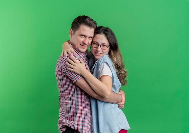 Молодая пара мужчина и женщина в повседневной одежде, счастливые в любви, обнимаются, стоя над зеленой стеной
