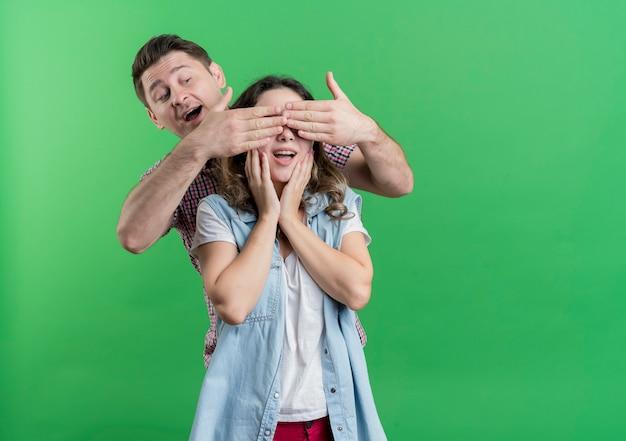 カジュアルな服を着た若いカップルの男性と女性が彼のガールフレンドの目を覆って緑に驚きを幸せな男