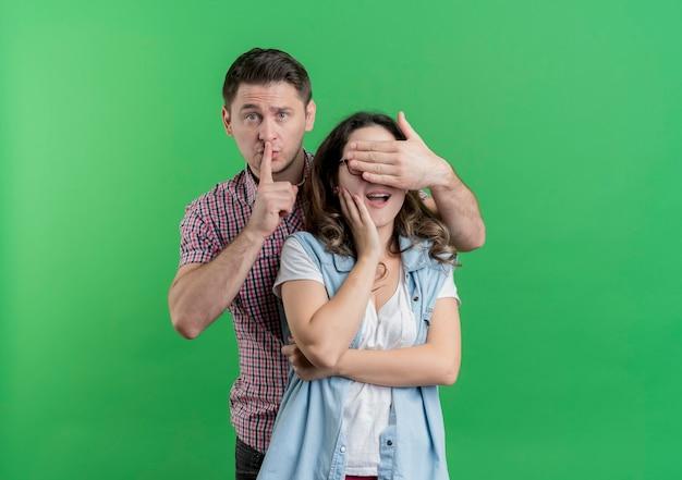 カジュアルな服装の若いカップルの男性と女性彼のガールフレンドの目を覆っている幸せな男は緑の上の唇に指で驚きを作る