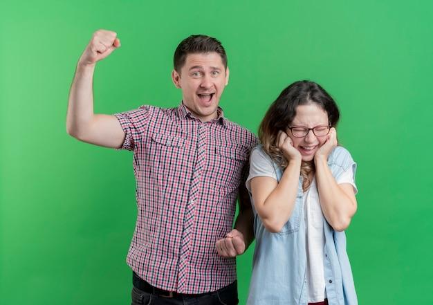 젊은 부부 남자와 여자 캐주얼 옷 행복한 사람이 주먹을 올리는 동안 그의 여자 친구는 녹색 벽 위에 미친 행복 서 기뻐하는 동안