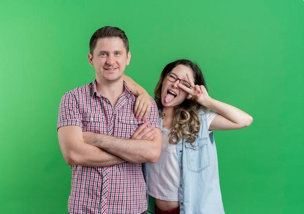 젊은 부부 남자와 여자 캐주얼 옷 행복한 사람이 녹색 벽 위에 v 기호 서 보여주는 그의 웃는 쾌활한 여자 친구 옆에 서