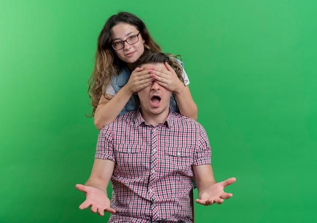 緑の壁の上に立って驚きを作る彼女のボーイフレンドの目を覆っているカジュアルな服を着た若いカップルの男性と女性幸せな女性