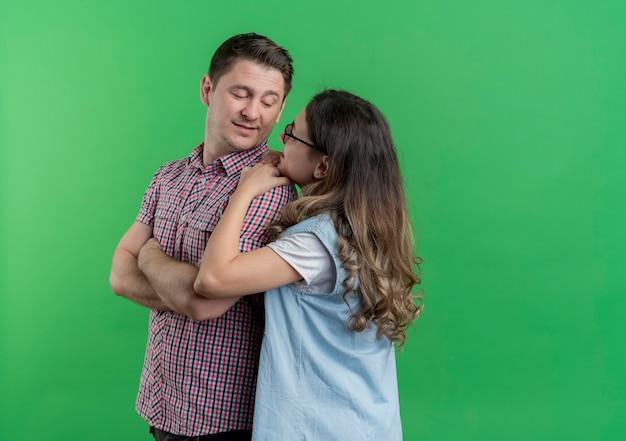 Молодая пара мужчина и женщина в повседневной одежде счастливая женщина обнимает своего любимого улыбающегося мужчину, стоящего над зеленой стеной