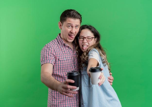 緑の壁の上に立っているコーヒーカップを見せて一緒に楽しんでカジュアルな服を着た若いカップルの男性と女性