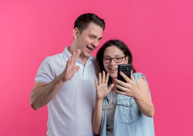 젊은 부부 남녀 캐주얼 옷을 입고 분홍색 벽 위에 유쾌하게 서있는 손을 흔들며 손을 흔들며