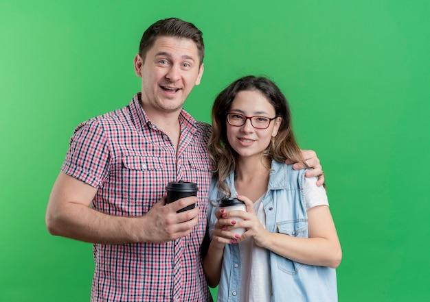 緑の壁の上に立って幸せで前向きな笑顔のコーヒーカップを保持しているカジュアルな服を着た若いカップルの男性と女性