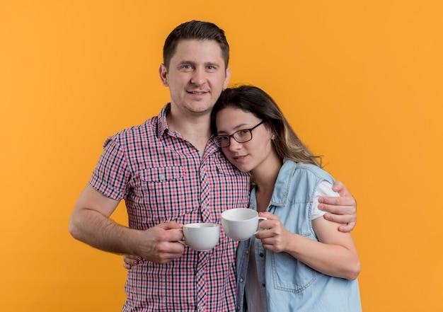 オレンジ色の壁の上に幸せで前向きに立っているコーヒーカップを保持しているカジュアルな服を着た若いカップルの男性と女性