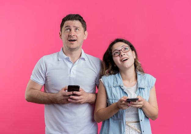 ピンクの壁の上に立って夢のような表情で見上げるスマートフォンを保持しているカジュアルな服を着た若いカップルの男性と女性