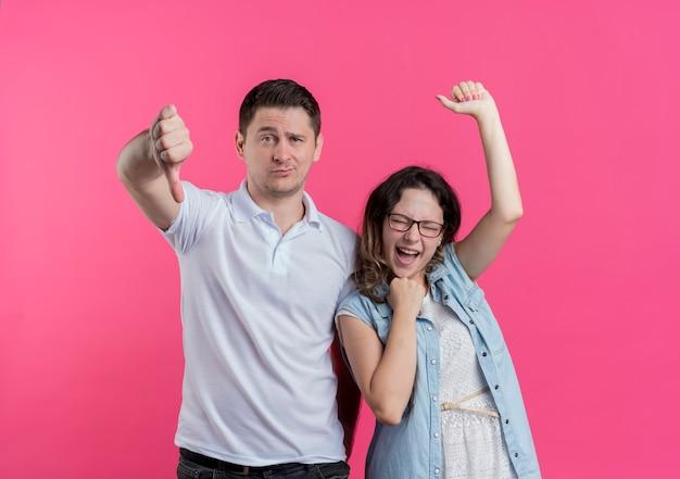 그의 여자 친구가 분홍색 벽 위에 행복하고 기뻐하는 동안 아래로 엄지 손가락을 보여주는 캐주얼 옷 남자 젊은 부부 남자와 여자