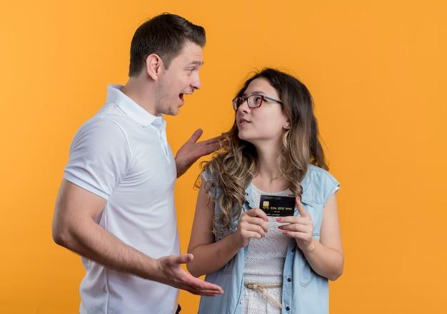 오렌지 벽 위에 서있는 그의 웃는 여자 친구와 이야기하는 캐주얼 옷 남자 젊은 부부 남자와 여자