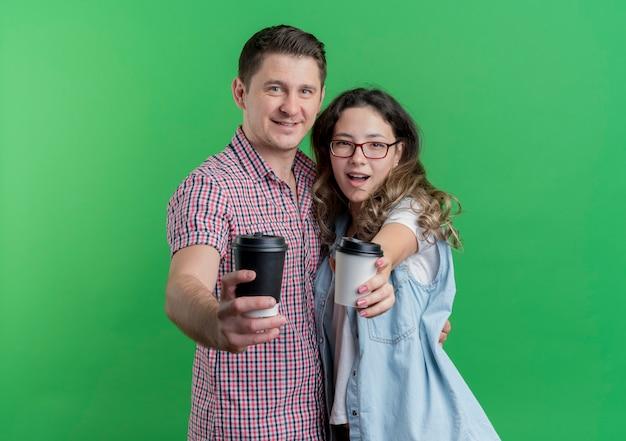 緑の壁の上に立って幸せで前向きな笑顔のコーヒーカップを示すカジュアルな服を着た若いカップルの男性と女性