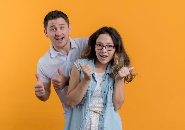 Молодая пара мужчина и женщина в повседневной одежде, весело улыбаясь, счастливы и взволнованы, показывая пальцы вверх, стоя над оранжевой стеной