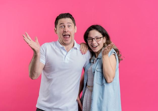 젊은 부부 남녀 캐주얼 옷을 입고 쾌활하게 행복하고 놀란 핑크색 벽 위에 서서