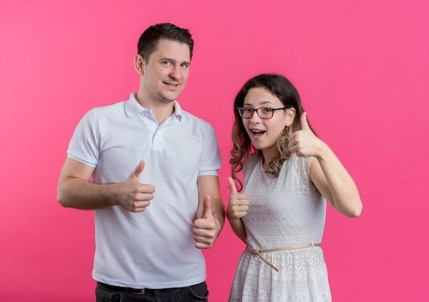 분홍색 벽 위에 서있는 엄지 손가락을 유쾌하게 보여주는 웃고있는 캐주얼 옷을 입은 젊은 부부 남녀