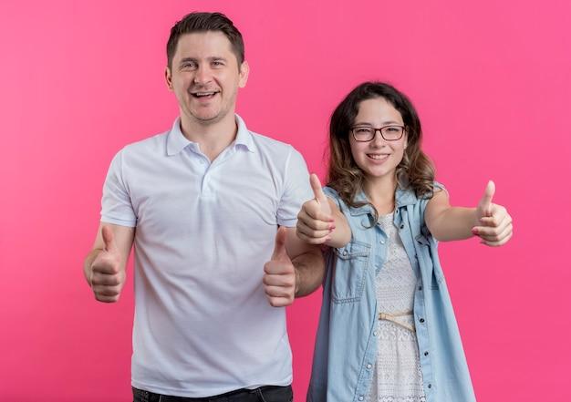 Молодая пара, мужчина и женщина в повседневной одежде, весело улыбаясь, показывает палец вверх, стоя над розовой стеной