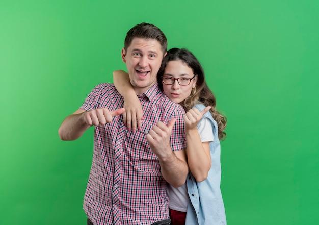 Молодая пара мужчина и женщина в повседневной одежде улыбается, показывает палец вверх, стоя над зеленой стеной