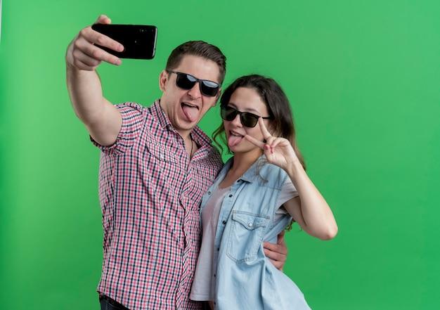 カジュアルな服を着た若いカップルの男性と女性が一緒に立って、緑の壁を楽しんで愛を幸せに自分撮りをしています
