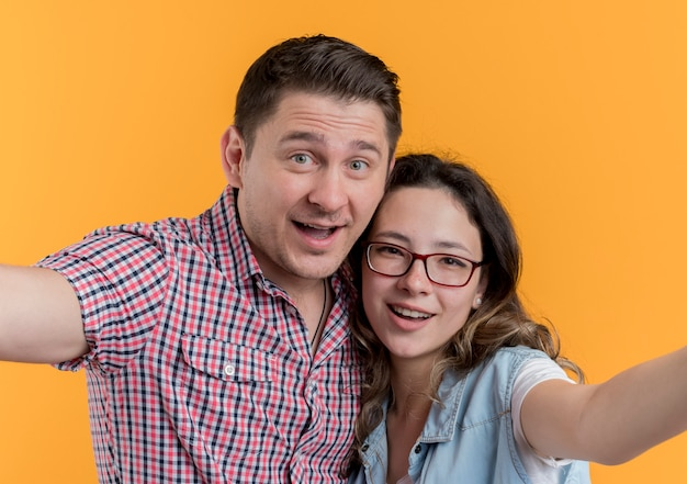 오렌지 벽에 재미 사랑에 행복 셀카 하 고 함께 서 캐주얼 옷에 젊은 부부 남자와 여자