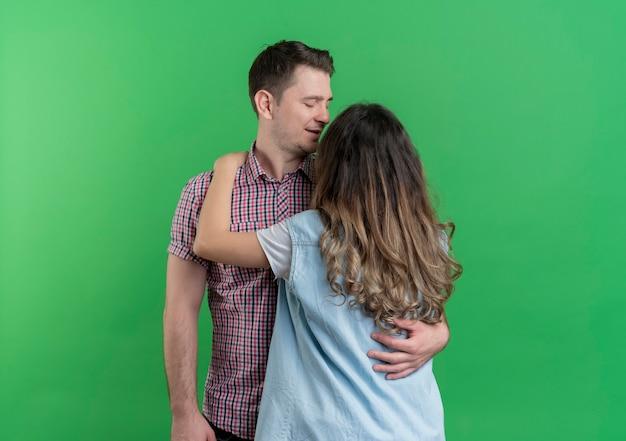 緑の壁の上に立って抱き締めて幸せに一緒に立っているカジュアルな服を着た若いカップルの男性と女性
