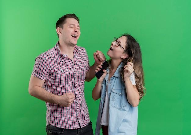 젊은 부부 남자와 여자 캐주얼 옷에 함께 서 녹색 벽 위에 행복하고 즐거운 재미