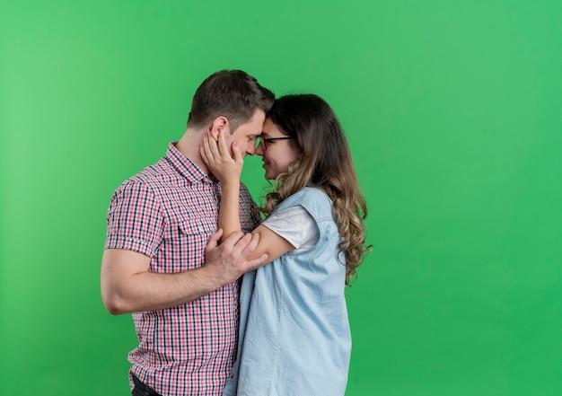 Молодая пара, мужчина и женщина в повседневной одежде, стоя вместе, обнимая счастливые в любви над зеленой стеной