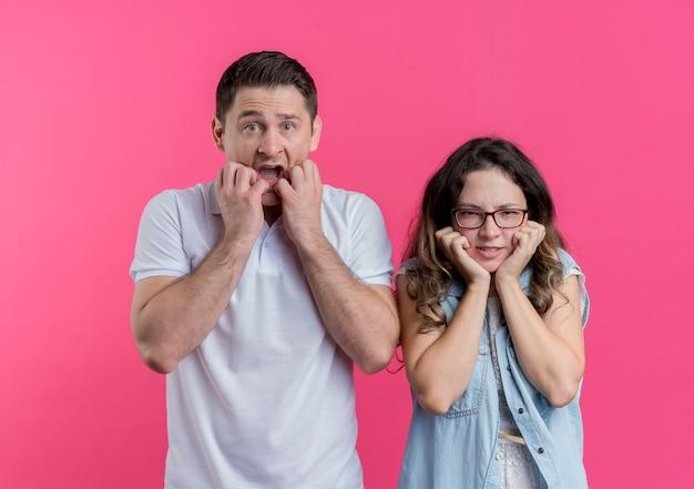 Молодая пара мужчина и женщина в повседневной одежде напряжены и нервно кусают ногти над розовым