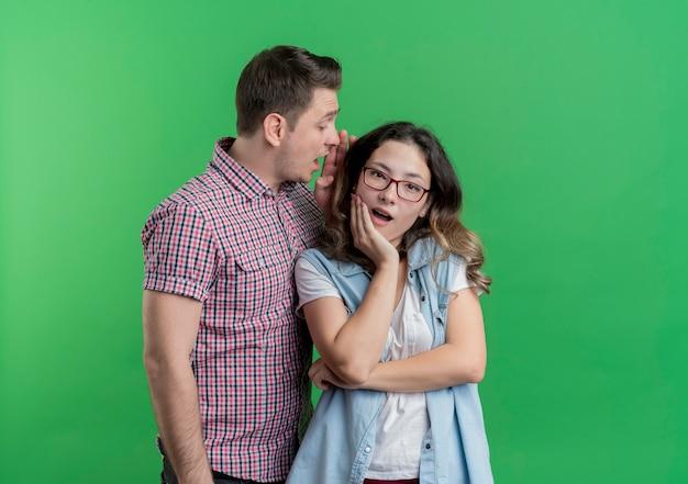 젊은 부부 남자와 캐주얼 옷에 여자는 녹색 벽 위에 서 그의 놀란 여자 친구에게 비밀을 속삭이는 남자를 놀라게