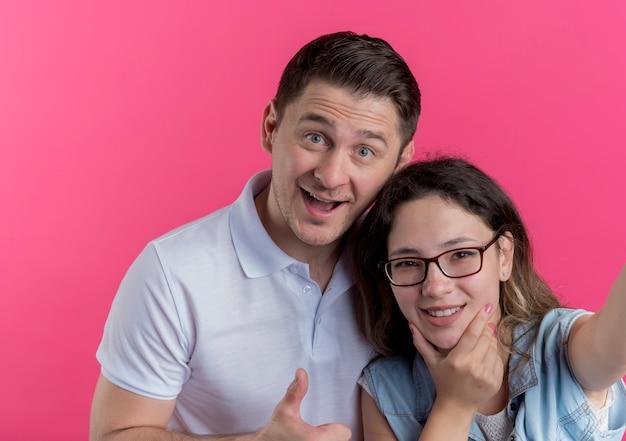 젊은 커플 남녀 캐주얼 옷을 입고 행복하고 긍정적 인 웃는 남자 핑크 위에 엄지 손가락을 보여주는