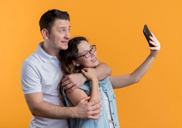 젊은 커플 남자와 여자 캐주얼 옷을 함께 오렌지를 통해 재미 사랑에 행복 셀카를하고