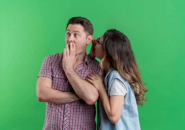 녹색 벽 위에 서있는 그녀의 놀란 남자 친구에게 비밀을 whispring 캐주얼 옷 여자 젊은 부부 남자와 여자