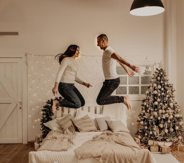 Молодая пара мужчина и женщина прыгают на кровати в спальне, украшенной деревом дом на новый год
