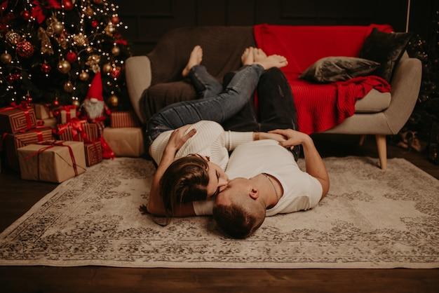 Молодая пара мужчина и женщина лежат на полу возле дивана с поднятыми ногами, обнимаются, целуются в спальне возле елки
