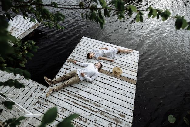 젊은 부부 남자와 여자는 호수에 물 근처 위에서 부두 사진에 거짓말.