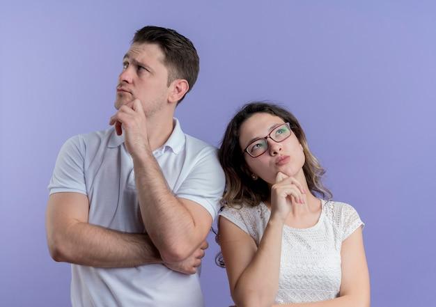 青い壁に立っている顔に物思いにふける表情で側近を探している若いカップルの男性と女性