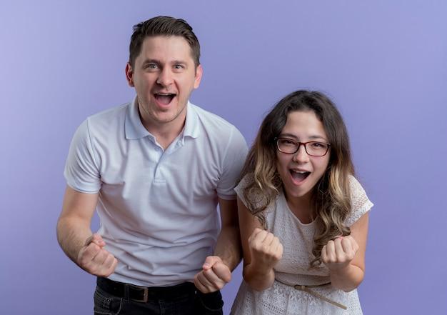 젊은 부부 남자와 여자는 파란색 벽 위에 서 행복하고 흥분 주먹을 떨림 카메라를보고
