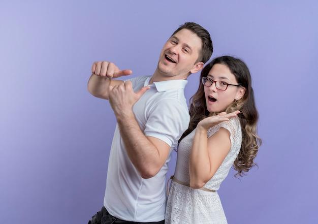 Молодая пара мужчина и женщина, глядя в камеру, весело улыбаясь, показывает палец вверх, стоя вместе над синей стеной