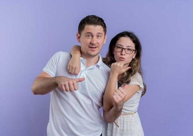 젊은 부부 남자와 여자는 파란색 벽 위에 유쾌하게 서있는 카메라를보고