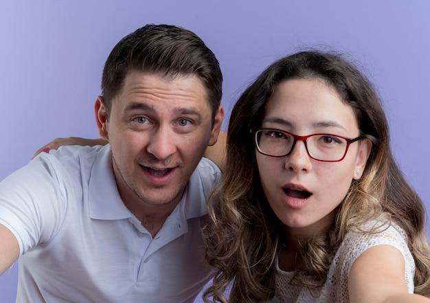 젊은 부부 남자와 여자는 파란색 벽에 행복하고 긍정적 인 미소를 카메라를보고