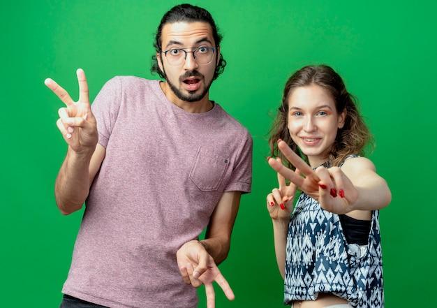 젊은 부부 남자와 여자는 녹색 배경 위에 서 승리 기호를 보여주는 미소 카메라를보고