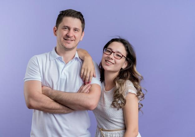 젊은 부부 남자와 여자는 파란색 벽 위에 유쾌하게 웃고 함께 서있는 카메라를보고