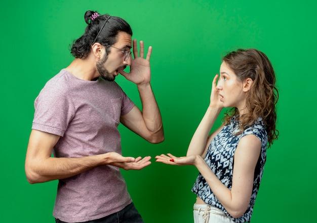 젊은 부부 남자와 여자는 서로를 찾고 녹색 벽 위에 서 혼란