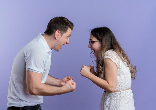 젊은 부부 남자와 여자는 파란색 벽 위에 서 서로 떨리는 주먹을보고