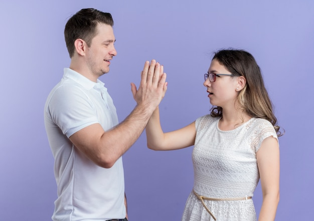 青い壁の上に立ってハイタッチを与えるお互いを見ている若いカップルの男性と女性