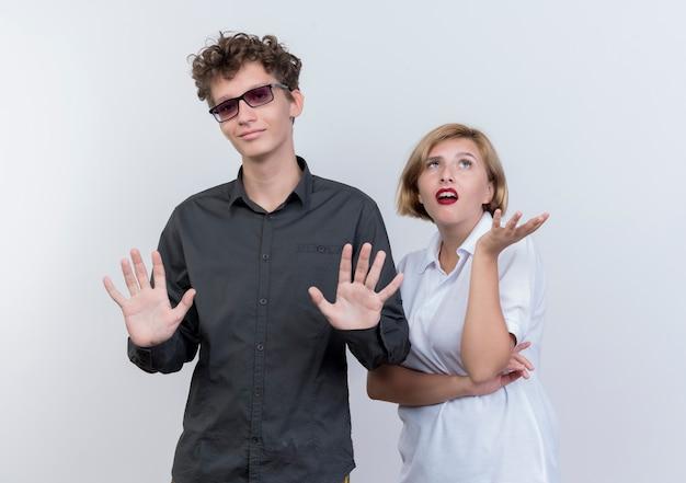 白い壁の上に立っている手で身振りで示す混乱と不満を探している若いカップルの男女
