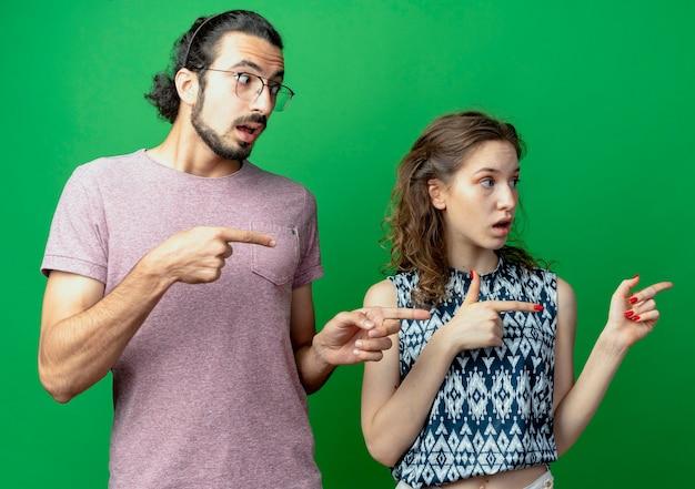 젊은 부부 남자와 여자는 녹색 벽 위에 서있는 측면에 검지 손가락으로 가리키는 혼란 찾고