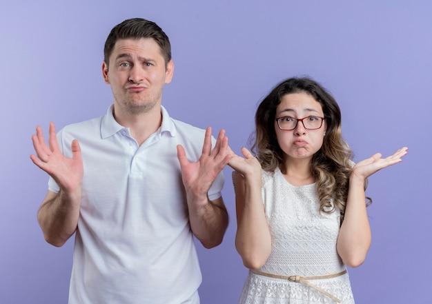 젊은 부부 남자와 여자는 파란색 벽 위에 서있는 어깨를 shrugging 혼란 찾고