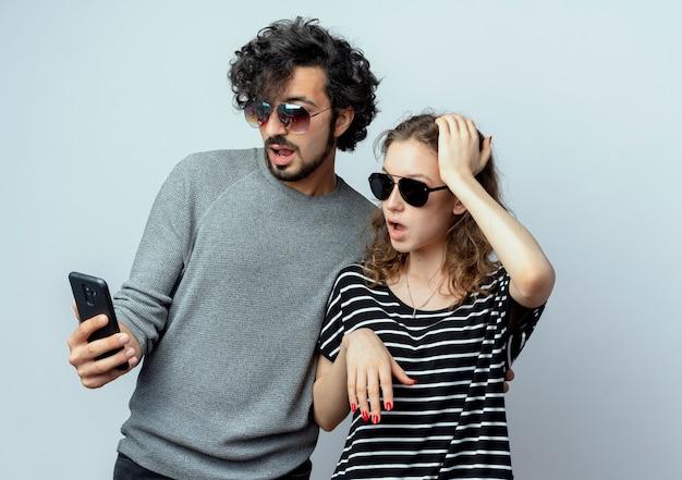 젊은 부부 남자와 여자는 흰색 배경 위에 서있는 스마트 폰의 화면에 놀란 찾고