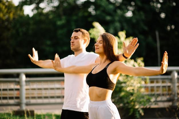 젊은 남녀는 서서 일몰을 함께 명상하고, 도시 잔디밭에서 요가, 여름 저녁, 생활 방식, 호흡 운동